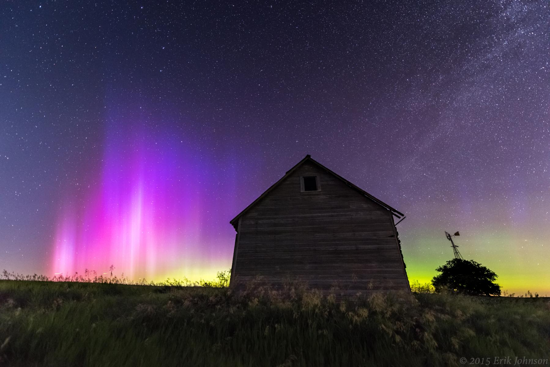 Aurora Borealis in the sky behind a wooden barn