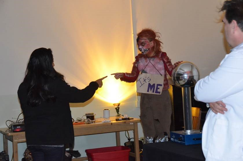 Girl in costume touches Van de Graaff generator
